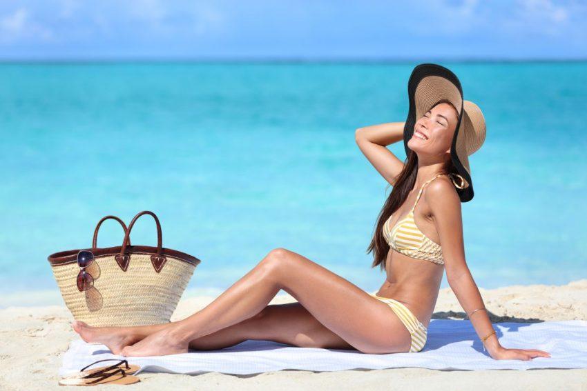 młoda kobieta w kapeluszu opala się na plaży