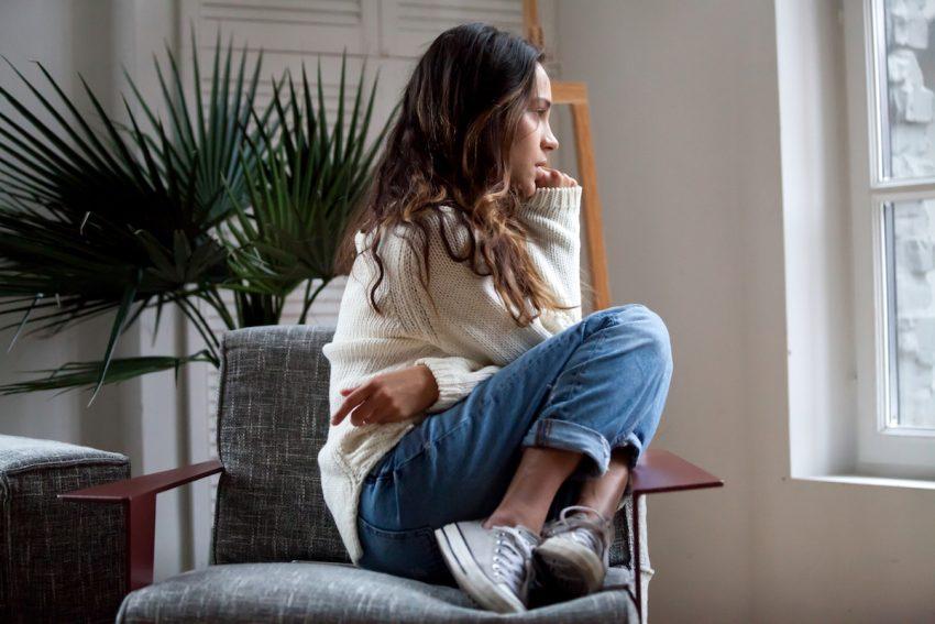Kobieta z zaburzeniami obsesyjno-kompulsywnymi spoglądająca przez okno.