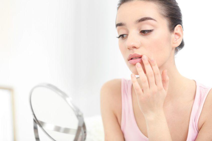 Kobieta z zajadami przegląda się w lustrze.