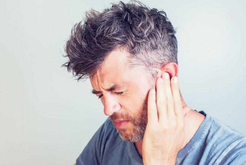 Mężczyzna trzyma się za ucho