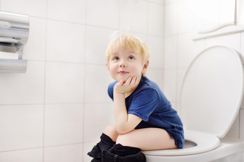 Chłopczyk mający zaparcie siedzi na ubikacji.