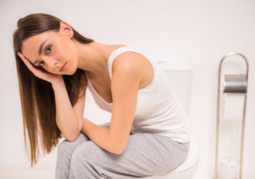 zasmucona młoda kobieta siedząca w toalecie na sedesie