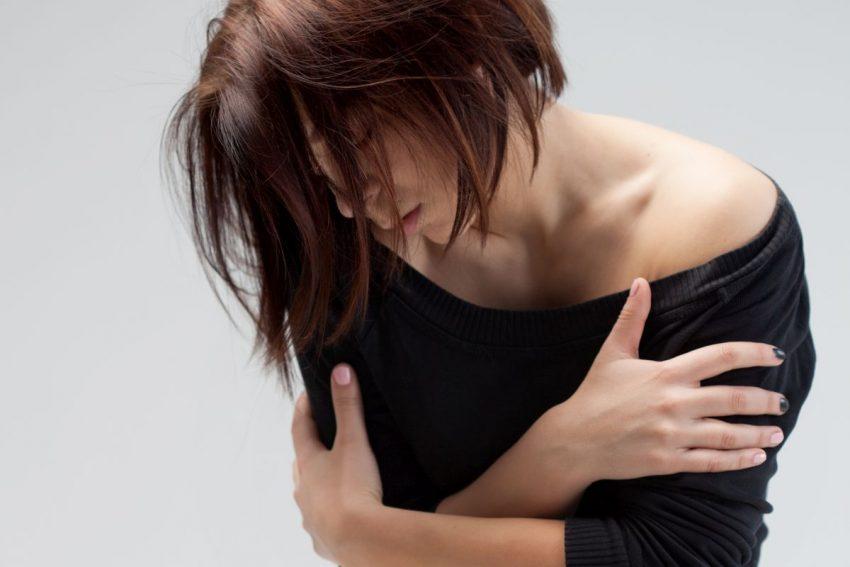 kobieta odczuwająca objawy zespołu abstynencyjnego trzymająca się za przedramiona