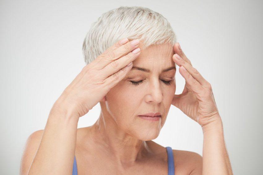 Kobieta w krótkich siwych włosach trzyma się za głowę