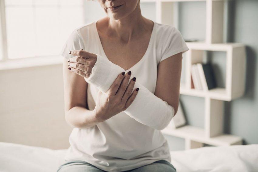 kobieta trzyma się za złamaną rękę w gipsie