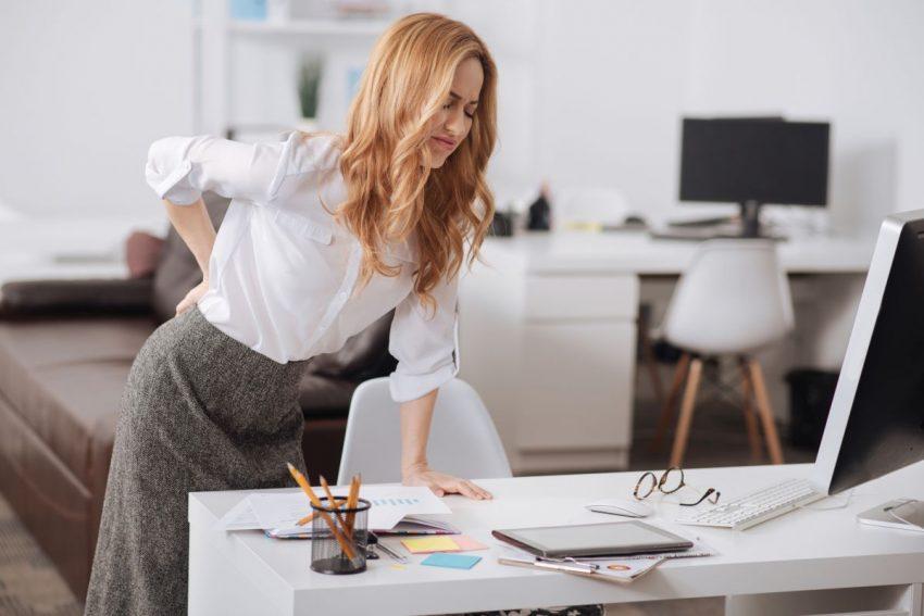 Kobieta w białej bluzce wstaje od biurka i trzyma się za plecy