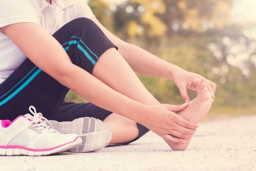 kobieta trzyma się za bolącą stopę