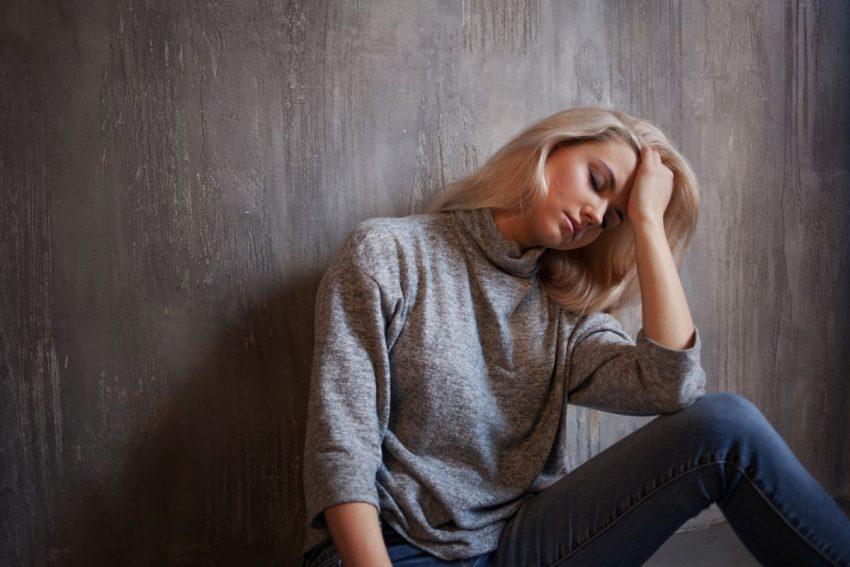 Kobieta siedząca pod ścianą i cierpiąca na hipernatermię