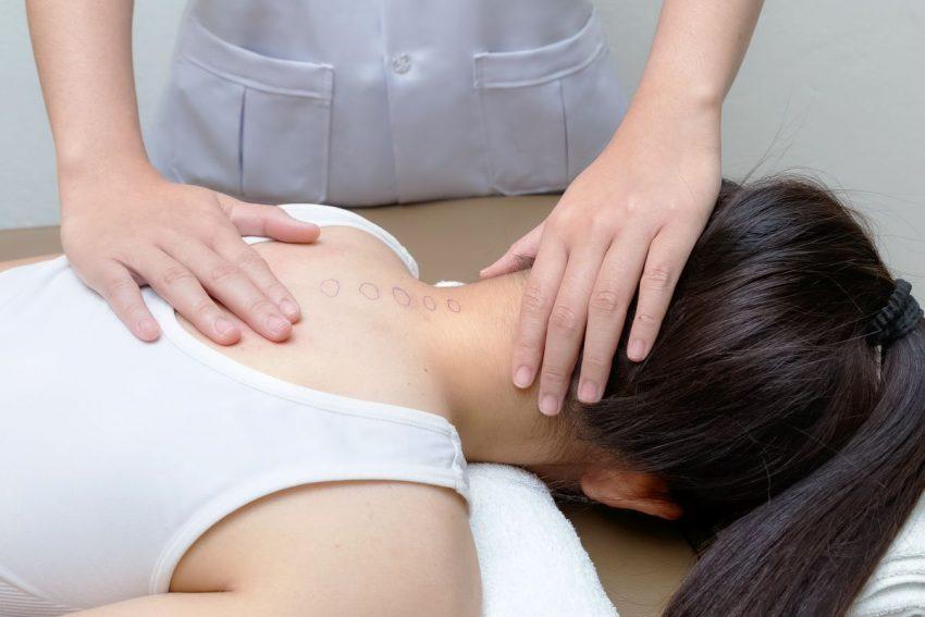 Kobieta cierpiąca na kifozę piersiową na masażu