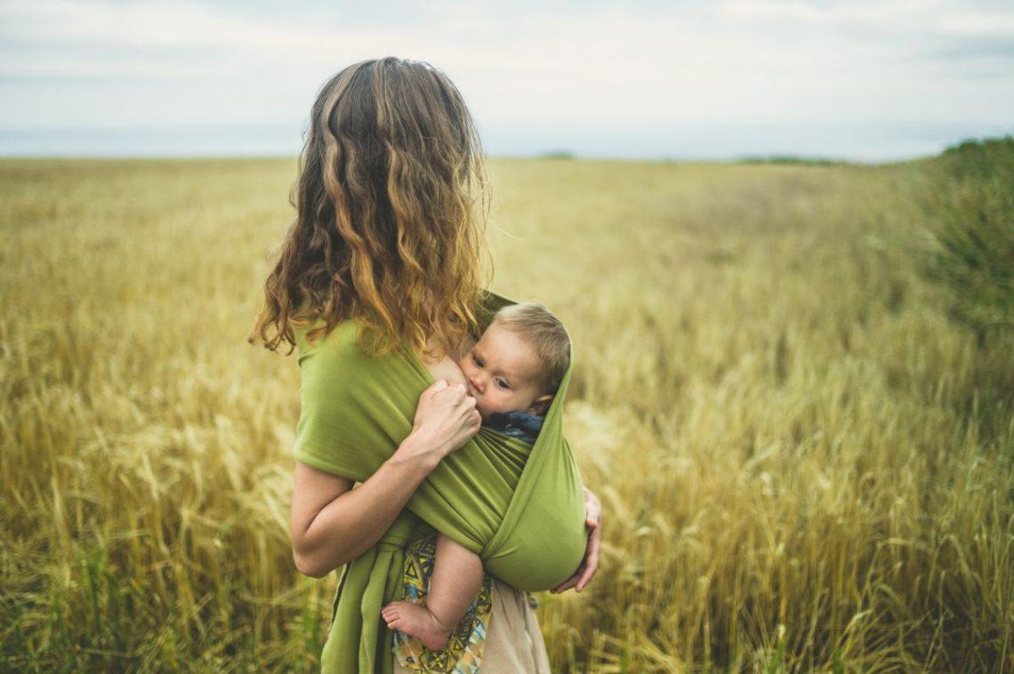 kobieta karmiąca dziecko piersią chodzi po polu