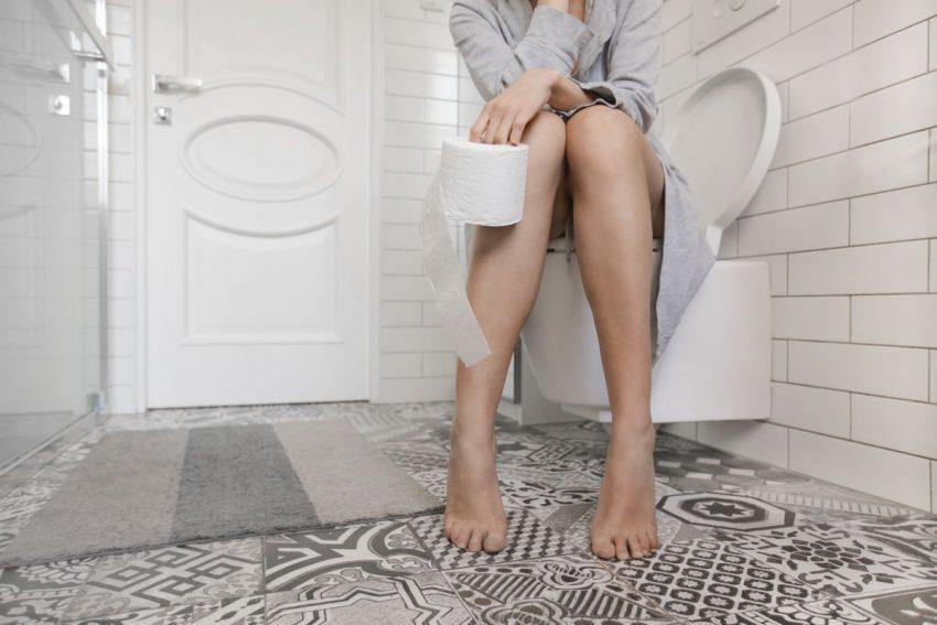 Kobieta siedząca na toalecie martwiąca się krwią w kale