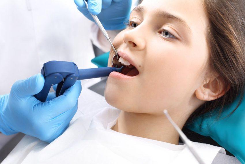 Dziewczynka u dentysty na zabiegu lakowania zębów