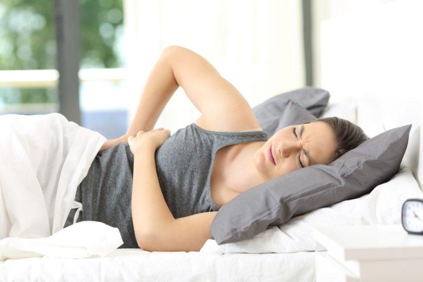 kobieta leżąca na łóżku kładzie dłonie na plecach z powodu lumbago
