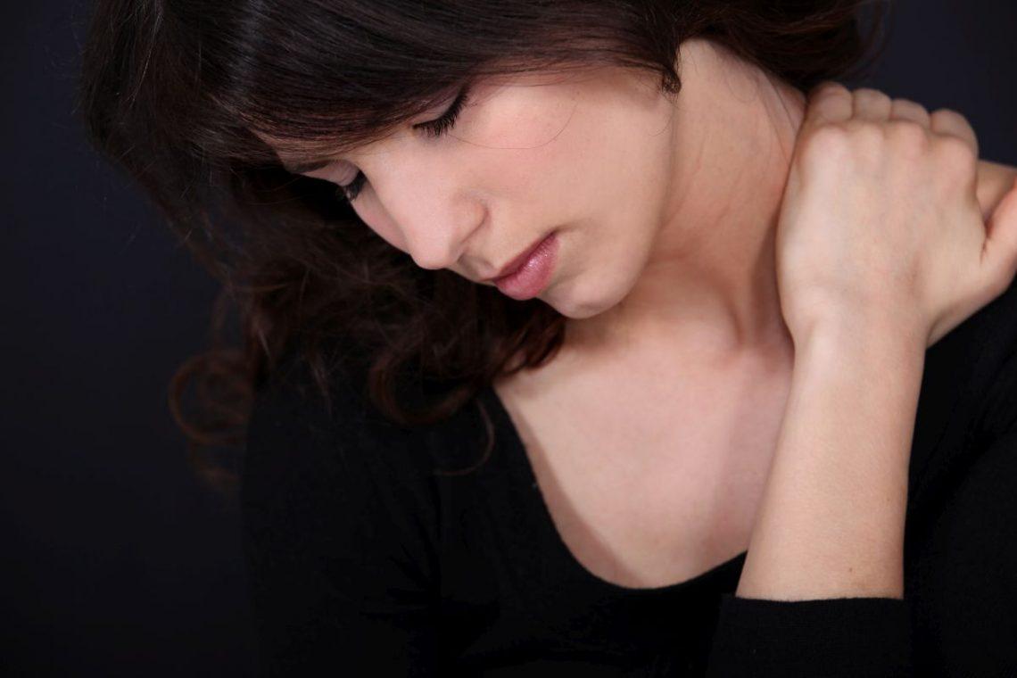 Kobieta trzymająca się za szyję z powodu mioklonii