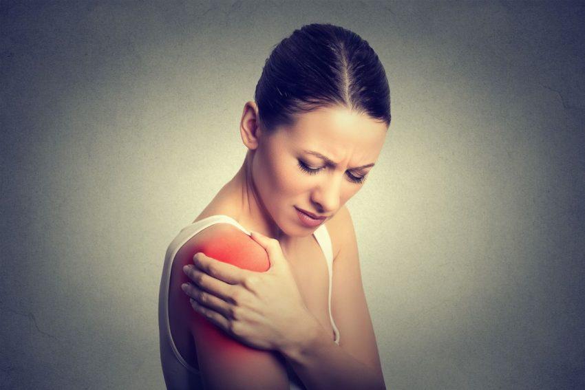 Kobieta z objawem Chełmońskiego, trzymająca się za ramię z powodu skurczu