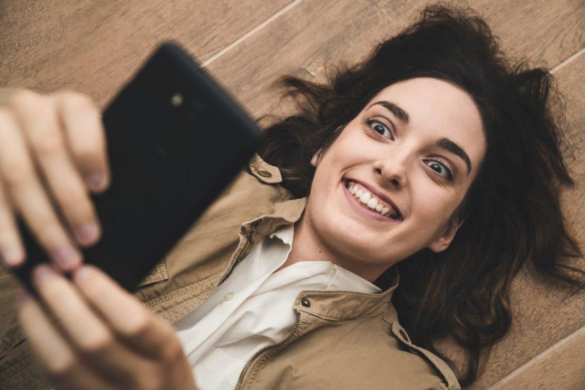 Kobieta cierpiąca na obsesję korzysta z telefonu komórkowego