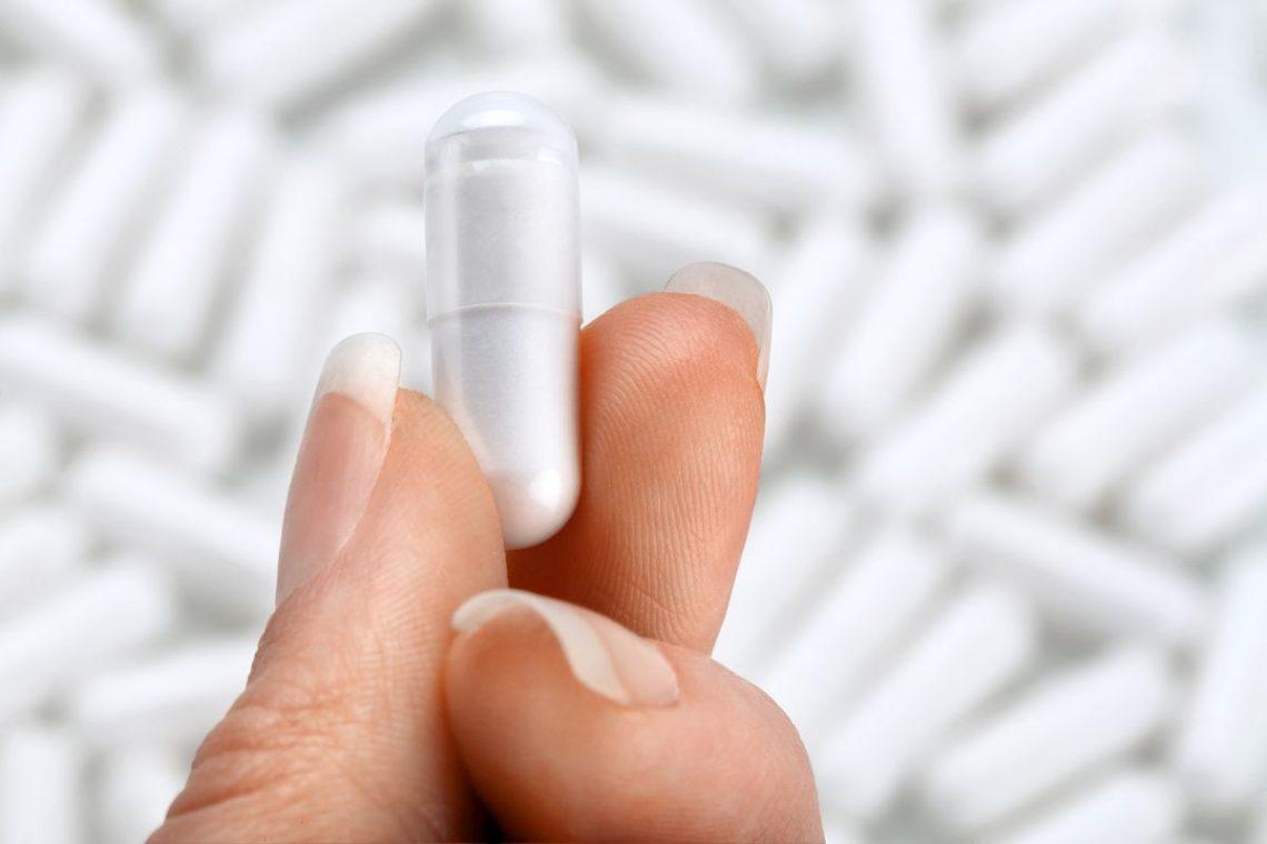 Kapsułka probiotyku trzymana w palcach