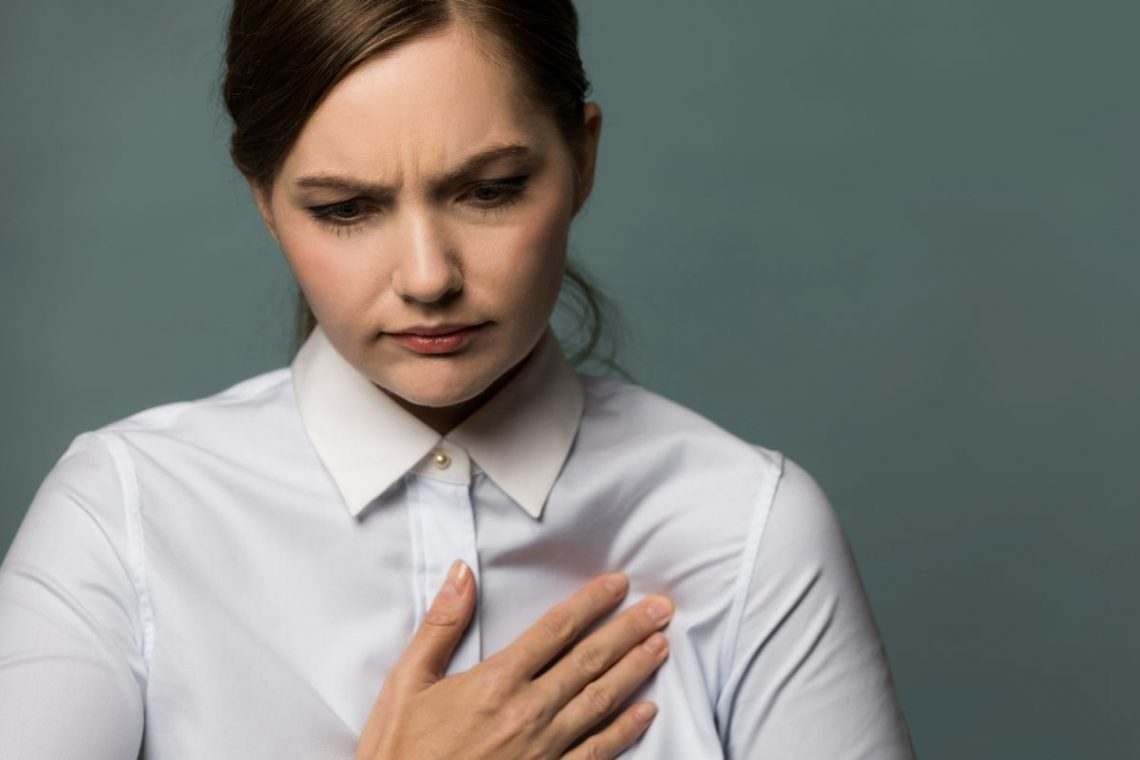 kobieta kładzie rękę na klatce piersiowej z powodu bólu wywołanego sercem płucnym
