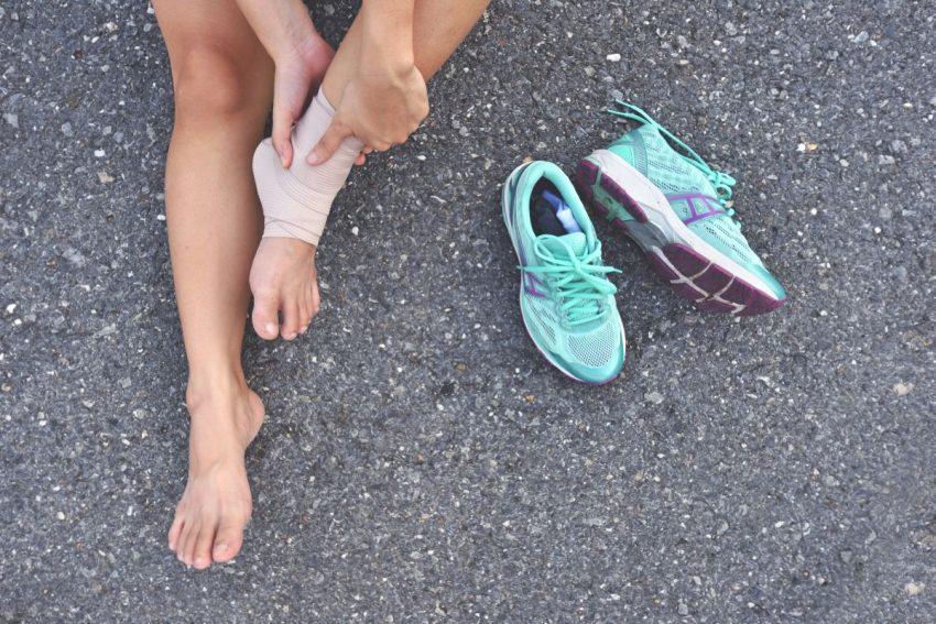 Biegacz ze zdjętymi butami sportowymi i skręconą kostką siedzi na ziemi