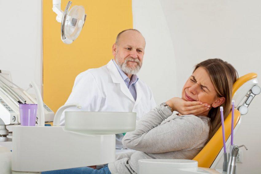 Kobieta będąca u dentysty, cierpiąca z powodu spuchniętego dziąsła