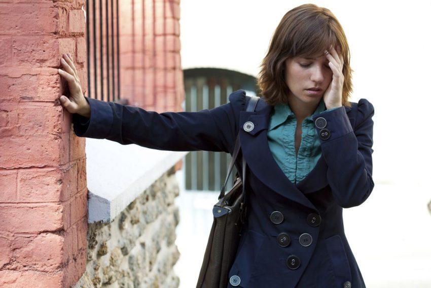 Kobieta opiera się o ścianę i czuje, że może zasłabnąć
