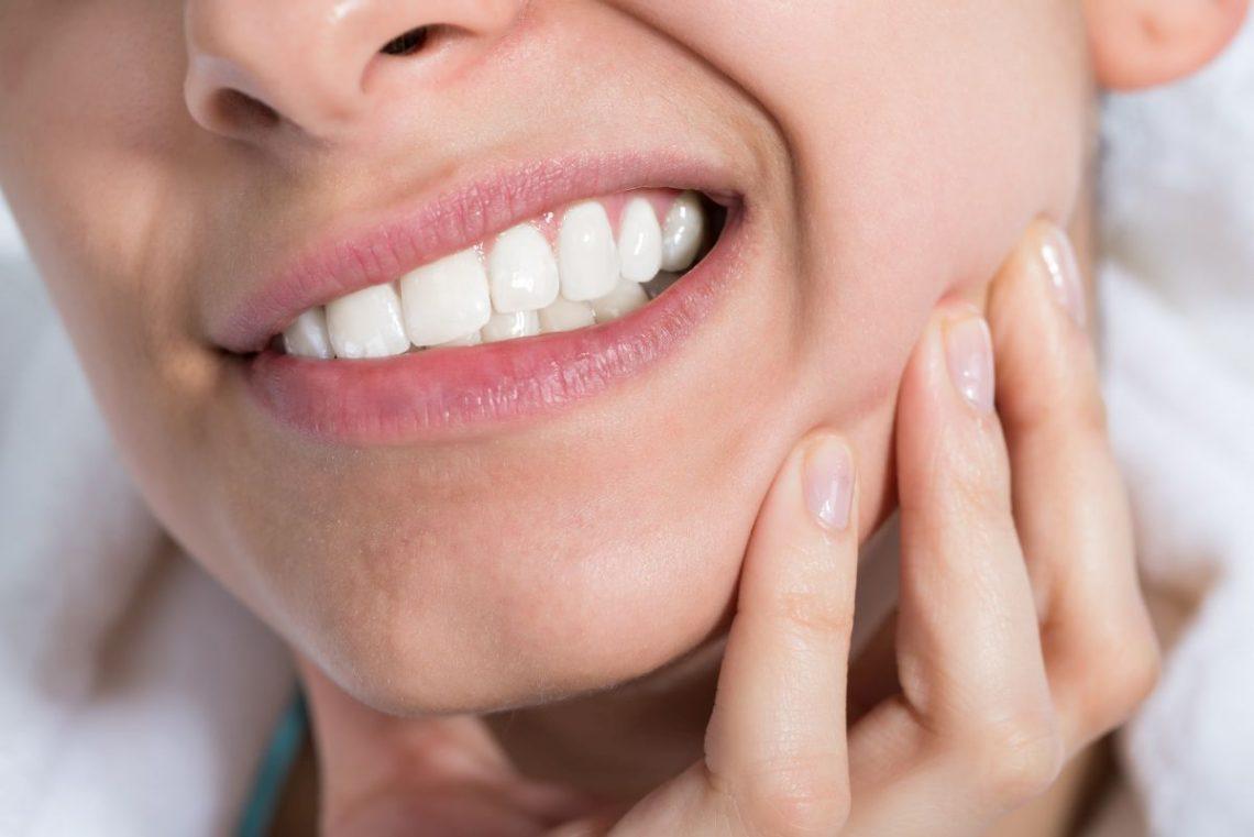 Kobieta z bolącymi zębami z powodu zgryzu otwartego