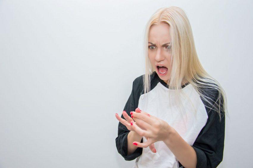 Kobieta krzywi się z powodu bólu spowodowanego złamanym palcem