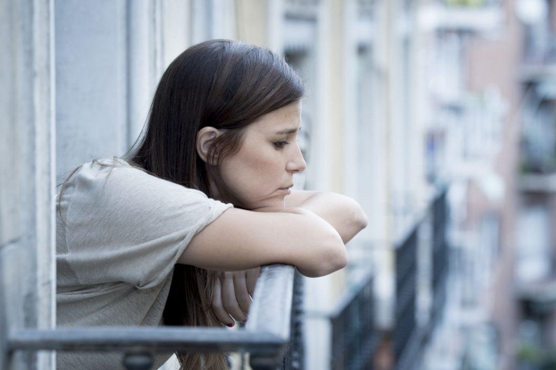 kobieta cierpiąca na abulię spogląda z balkonu na ulicę