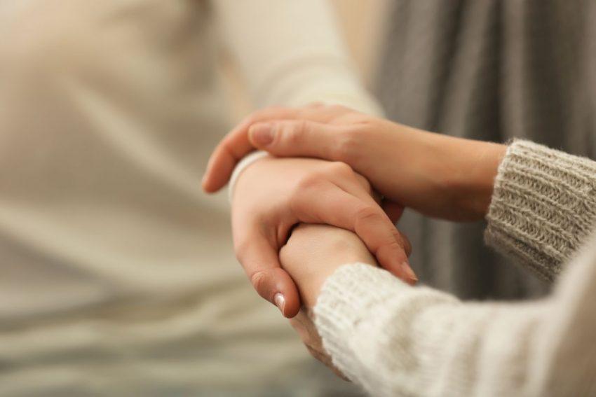 kobieta obejmuje za dłoń osobę cierpiącą na atetozę