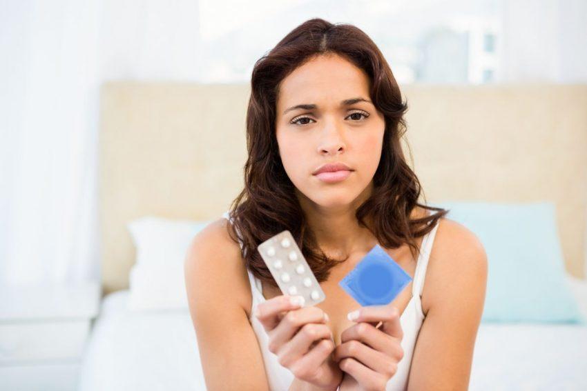 kobieta trzymająca w rekach środki antykoncepcji zastanawia się które z nich jest skuteczniejsze, na podstawie wskaźnika Pearla