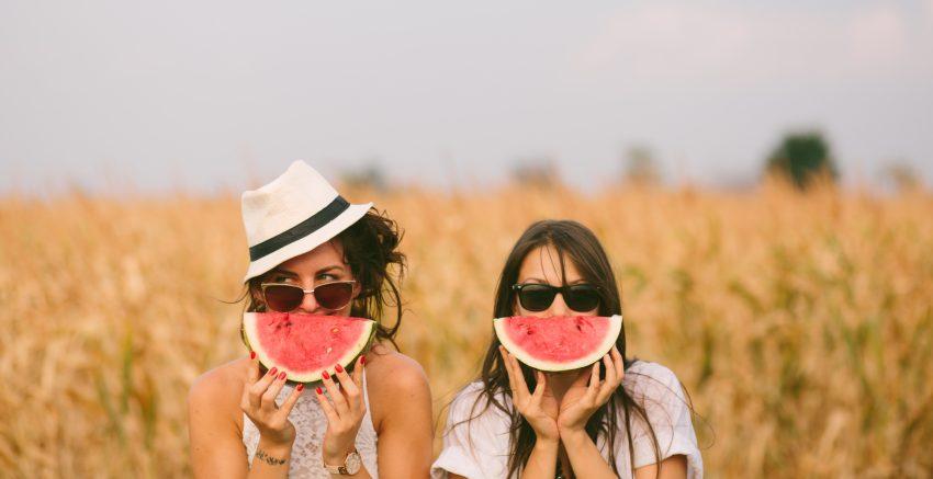 Dwie dziewczyny trzymają arbuzy przy twarzy