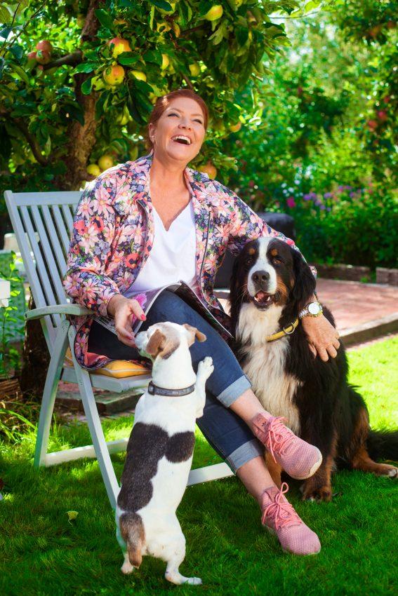 Katarzyna Dowbor w ogrodzie z psami