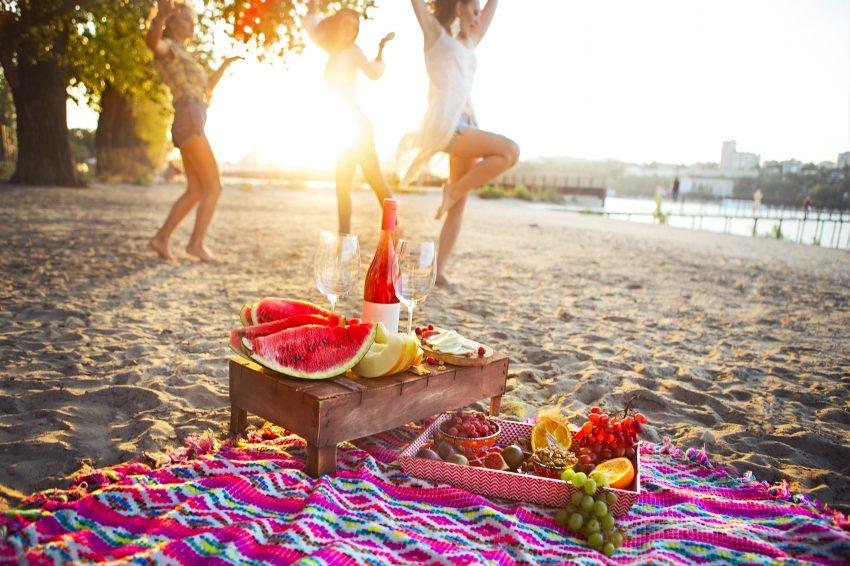 Trzy kobiey tańczą na plaży. Przed nimi koc a na nim owoce i drink