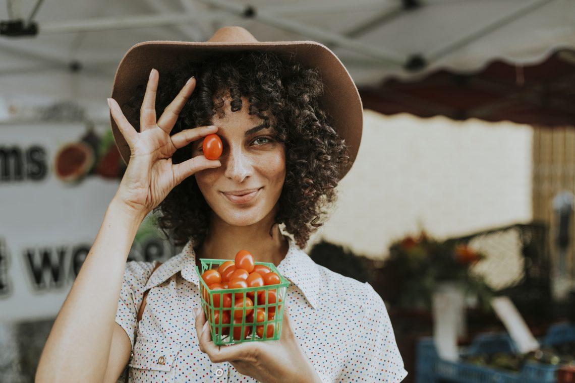 Kobieta w kapeluszu i kręconych włosach stoi na targu,patrzy się na nas,, w jednej ręce ma kubek z pomidorami, w drugiej trzyma jednego pomidora zakrywając sobie nim oko