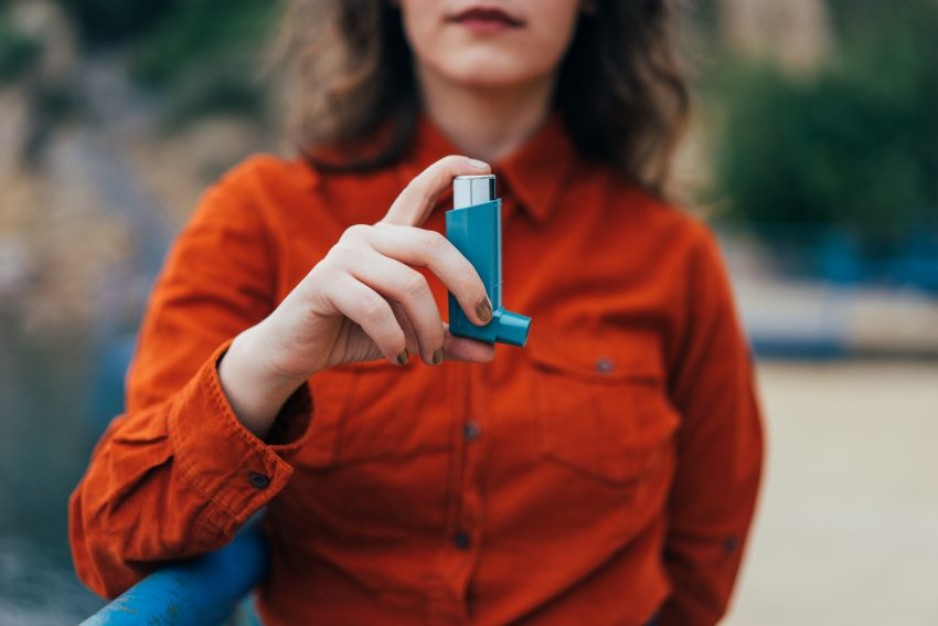 Kobieta ma astmę i trzyma w ręce inhalator, który jest na pierwszym planie.