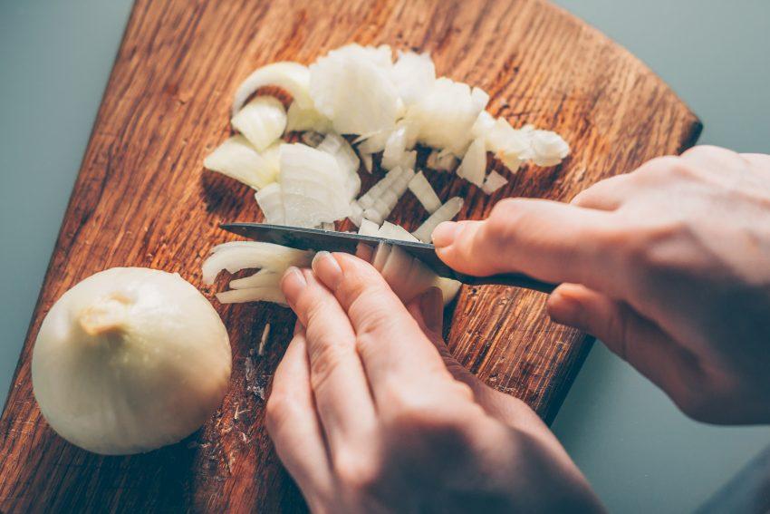 Ręce, które kroją cebulę nożem na drewnianej desce