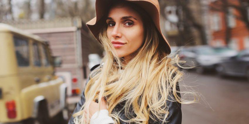 Kobieta w kapeluszu stoi na ulicy