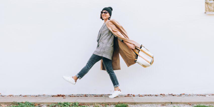 Kobieta podskakuje, idąc chodnikiem. Ubrana jest w jeansy, żakiet, płaszcz, trampki, czapkę i okulary przeciwsłoneczne. Wymachuje torebką. Uśmiecha się