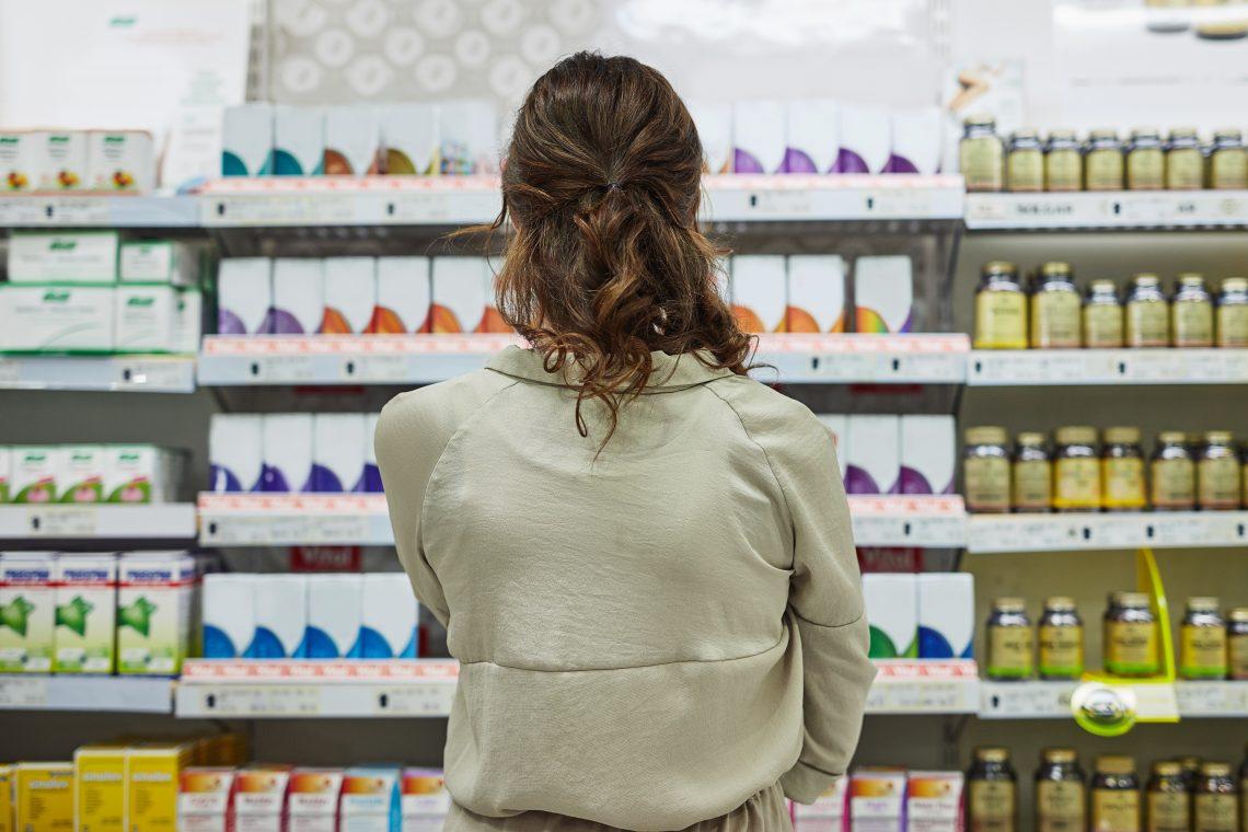 Kobieta stoi w aptece i patrzy się na leki