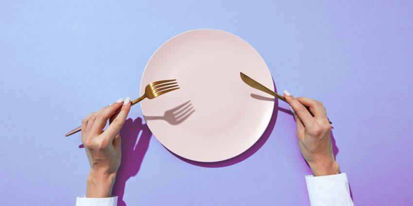 Biały talerz, osoba trzyma w dłoniach widelec i nóż