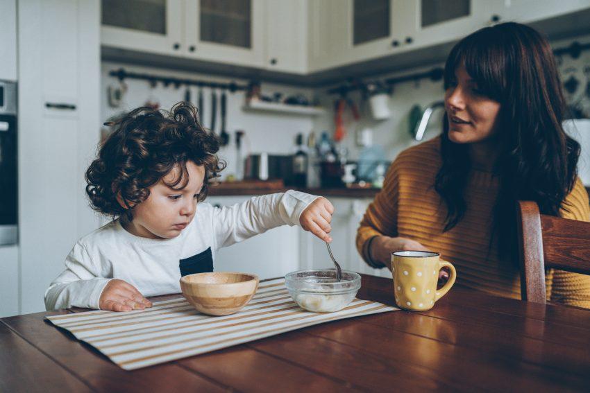 Kobieta z dzieckiem siedzą przy stole w kuchni. Mama pije kawę a dziecko je z dwóch salaterek śniadanie