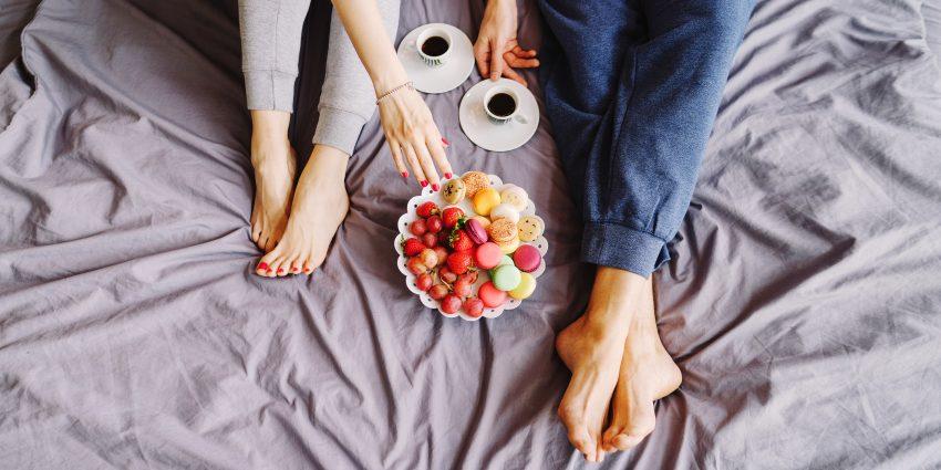 Dziewczyny jedzą słodycze i owoce na łóżku