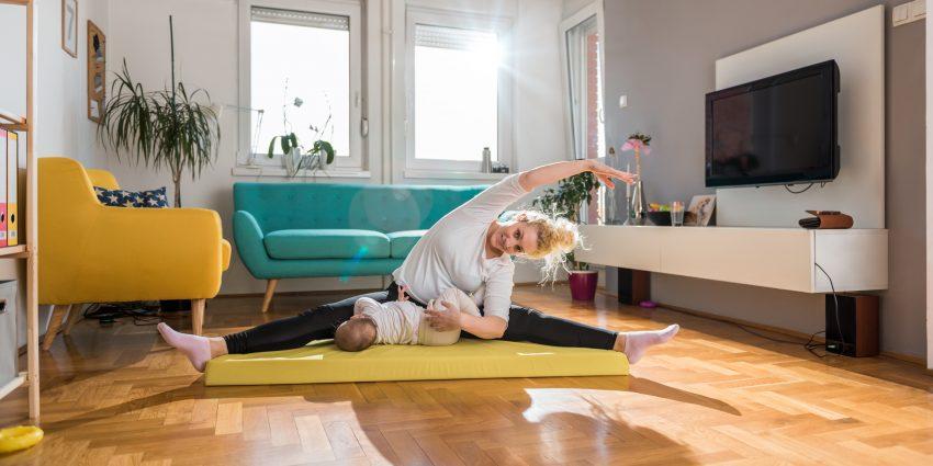 Kobieta ćwiczy na macie w pokoju. Obok leży małe dziecko