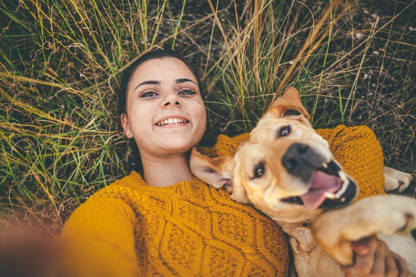 Kobieta leży na trawie, przytula psa