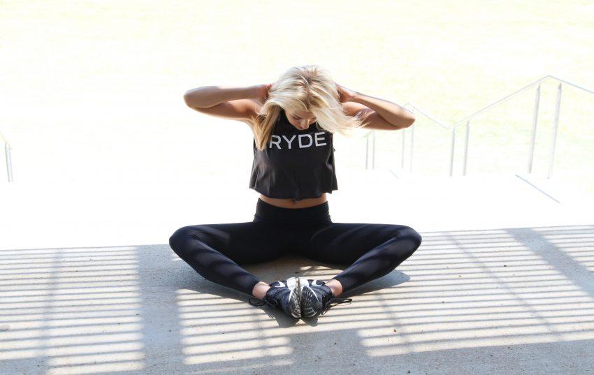 Kobieta siedzi na podłodze i ćwiczy. Ręce ma na karku, głowę pochyloną, nogi rozłożone na boki, stopy przy sobie