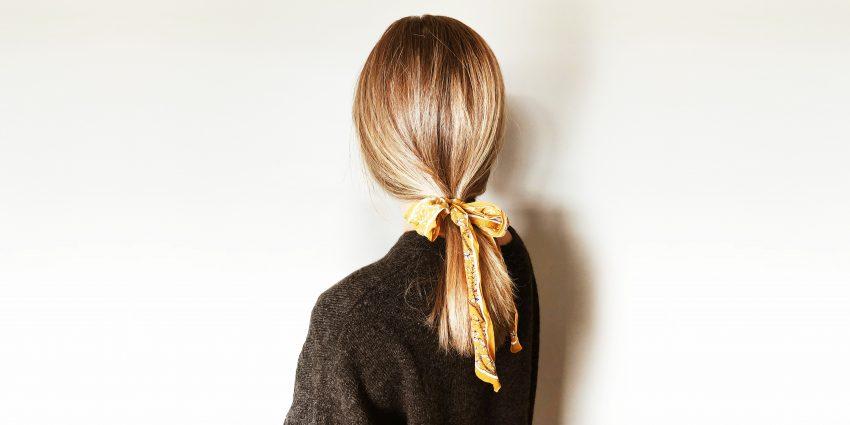 dziewczyna uczesana w kitkę związaną kokardą stoi tyłem ubrana w sweter