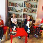 Dzieci z nowotworem siedzą przy stoliku na krzesełkach i czytają książki, uśmiechają się