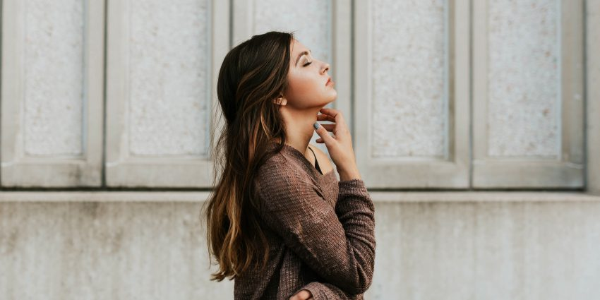 młoda kobieta z ręką na szyi