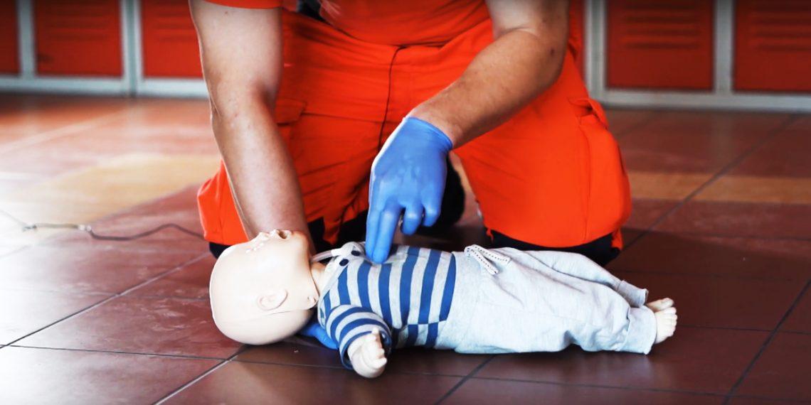 Mężczyzna uciska klatkę piersiową na manekinie noworodka, aby pokazać jak przeprowadzić pierwszą pomoc
