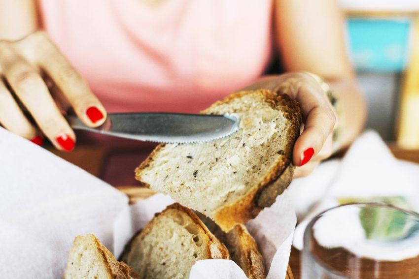 Kobieta smaruje kromkę chleba masłem
